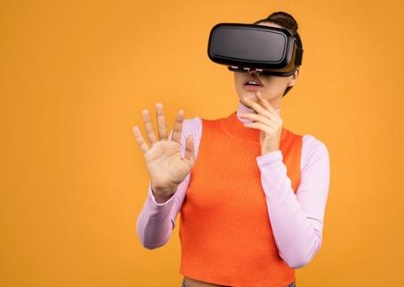 Frau mit 3D Brille vor orangem Hintergrund